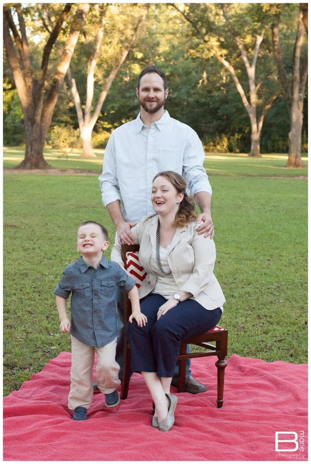 Family portraits in a park on a red blanket