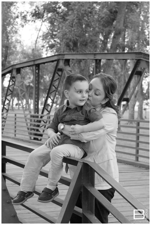 Family portraits in a park, mom and son on bridge